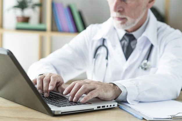 doctor on his laptop - work comp cases decreasing during the pandemic?